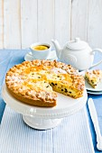 Greek ricotta crostata with chocolate chips on a cake stand