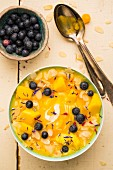 A 3-D bowl with mango, pineapple, yoghurt, blueberries, flaked almonds and petals