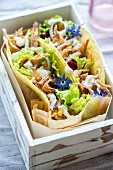 Tortillas filled with pulled pork, lLettuce and vegetables in a wooden crate