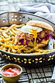 A burger with pulled pork, Cheddar, avocado cream, a poached egg and celeriac chips