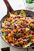 Gratinated nachos with pulled pork. Cheddar and beans