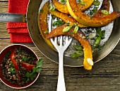 Roasted pumpkin wedges with tomatoes and lentils