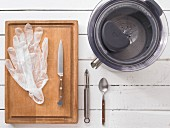 A juicer, disposable gloves, a knife, a peeler and a spoon