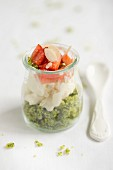 A layered cake dessert in a glass jar with spinach cake, cream and strawberries