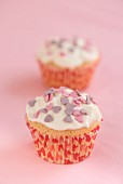Cupcakes topped with cream and decorated with sugar hearts