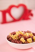 A bowl full of heart-shaped pasta with the word 'LOVE' in the background