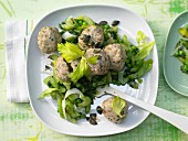 Bread dumplings on a bed of vegetables with chives and pumpkin seeds