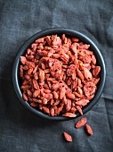 Goji berries (lycium barbarum) in a bowl on a dark surface