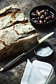 An arrangement of crusty bread, olives, sea salt, a knife and a fabric napkin