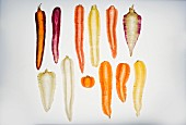 Twleve assorted carrots sliced lengthways on a transparent surface