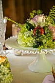 Festive flower arrangement with strawberries on white cake stand