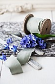 Ribbon on wooden reel, cutlery and hyacinths on table