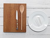 Plate, toothpicks, cooking spoon and knife