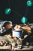 Heiße Schokolade mit Sahne, Kakaopulver und Zimt, dazu Lebkuchen und Nüsse auf Holztablett