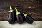 Three aubergines in front of a wooden wall