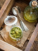 Vegan coriander and parsley pesto in a small jar on a wooden surface