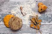Verschiedene frische Brote auf altem Holztisch mit Mehl und Serviette