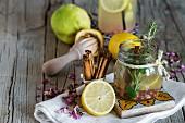 Limonade mit frischer Zitrone, Minze, Zimt und Quitte auf Holzuntergrund