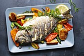 Gilt-head bream with rosemary on a bed of oven-roasted vegetables