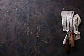 Vintage kitchenware kitchen utensils Meat Fork and Butcher Cleaver on dark background