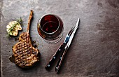 Grilled beef barbecue Veal rib Steak on bone and wine on stone slate background