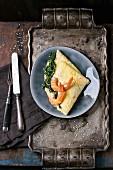 Omelett mit Spinat und gebratenen Garnelen, serviert mit Sesam