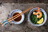 Spinach with pan-fried prawns, lemon and sesame seeds next to a bowl of soy sauce and chopsticks