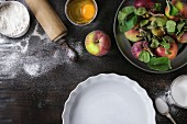 Ingredients for making apple cake: flour, sugar, a whisked egg, fresh apples, a white flan dish and a rolling pin