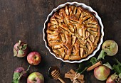 Apple cake pie in a white ceramic flan dish with fresh apples, honey and cinnamon sticks