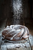 A Bundt cake on a wooden table being dusted with icing sugar