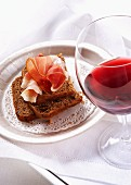 Chestnut bread with cured ham and a glass of red wine