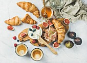 Breakfast with croissants, ricotta, figs, berries, ham, honey and espresso