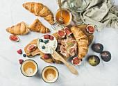 Frühstück mit Croissants, Ricotta, Feigen, Beeren, Schinken, Honig und Espresso