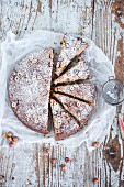 An apple and hazelnut cake with icing sugar, sliced