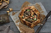 An artichoke and chanterelle mushroom galette on baking paper (seen from above)