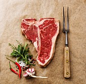 Raw fresh meat T-bone steak, seasoning and meat fork on cooking paper background