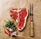 Rohes T-Bone-Steak, Gewürze und Fleischgabel auf Papier