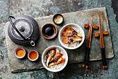 Eel with sauce and sesame seeds on a bed of rice with chopsticks, a teapot and tea bowls