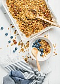 Porridge oats with pecan nuts, blueberries and yoghurt in a bowl on a white wooden surface