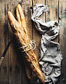 Two French baguettes on a rustic wooden surface