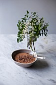 Chocolate mousse sprinkled with grated dark chocolate in a small bowl on a white marble table