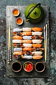 A Nigiri sushi set for two on a grey slate slab with chopsticks and green tea