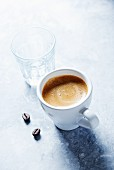A cup of espresso, glass of water and coffee beans
