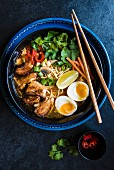 Japanese ramen noodle soup with slow cooked pork, coriander and egg