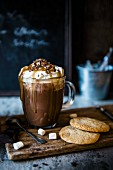 A mug of hot chocolate with whipped cream and toffee sauce next to biscuits and marshmallows