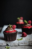 Dark chocolate and raspberry cupcakes with mint leaves