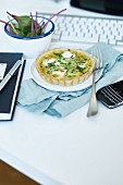 A small quiche with peas and goats' cheese on a desk