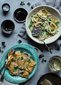 Ravioli with herbs and Parmesan on two plates in a vintage setting