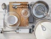 Kitchen utensils for preparing a green salad with poached egg, ham, dressing and croutons