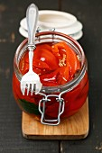 Pickled peppers in a glass jar with a fork on a chopping board